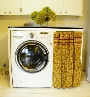 Built in laundry storage with a curtain and an enamelware countertop