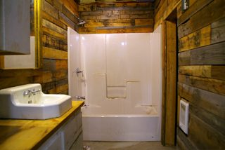 Covering the walls of my basement bathroom with pallet and barn wood instead of sheet rock during the renovation of my basement workshop
