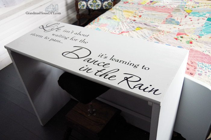"""A little black desk gets a full on farmhouse country girl style makeover with flat gray acrylic paint and a lovely wall decal """"Life isn't about waiting for the storm to pass, it's learning to Dance in the Rain"""" Easy DIY farm chic style makeover! Farmhouse Hens Decorate"""
