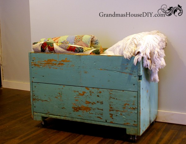 My grandma's old carrot box gets repurposed into our living room shabby chic storage bin for dvds and blankets