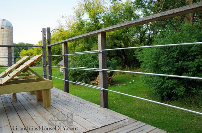 DIY inexpensive how to deck rails out of steel conduit to look like steel wire deck railings, tutorial on how we did the railings on our deck!