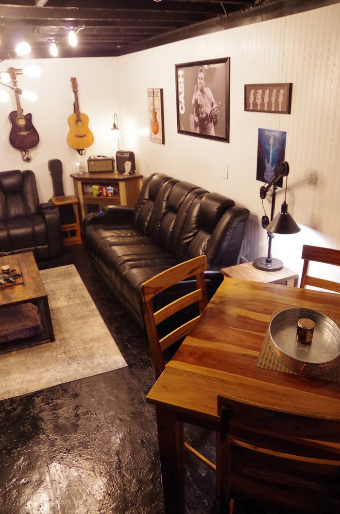 Basement living room reveal a completely finished Edison bulb speak easy and guitar space for listening to music, drinking and relaxing