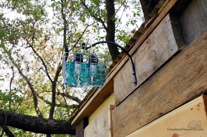 A basket solar light made with old electrical insulators and dolalr store lights placed in an ainexpensive Amazon basket to hang or for table setting