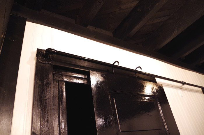 How to inexpensively create rolling barn door hardware with salvaged doors, black pipe and PVC. Moving back to completing our basement