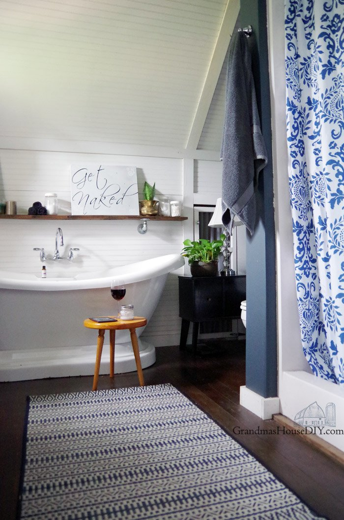 With a new rug, shower curtain, shelf my master bathroom refresh combines bohemiam style with farmhouse chic! Adding life with a double slipper bathtub