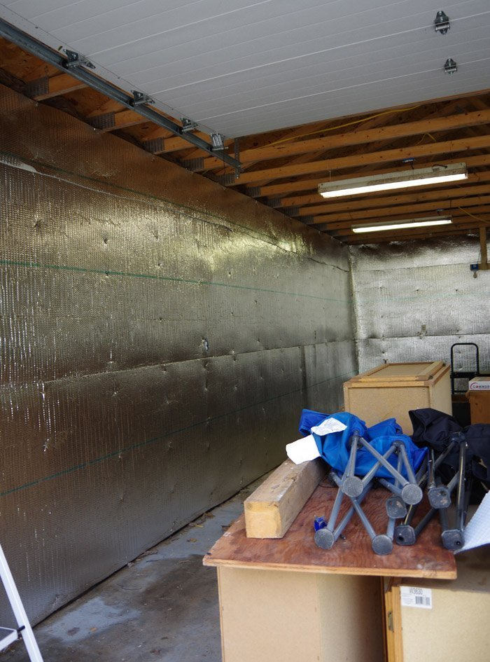Covering my garage walls with plastic and then bubble wrap insulation with help from two friends on a hot day before moving on to hanging a door