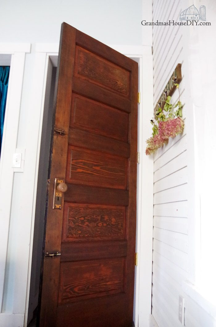 How to refinish a door by sanding down and restaining on one side and painting it out with two coats of gloss rustoleum black paint on the other side. Reusing, recycling, solid wood antique door with old brass knob for my new guest bedroom and library.