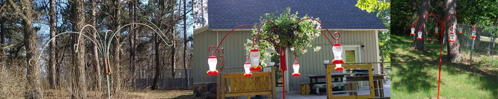 Hummingbird feeder planter shepherds hook extravaganza painted bright red with six humming bird feeders hanging from it. And a whit flowering plant scaevola