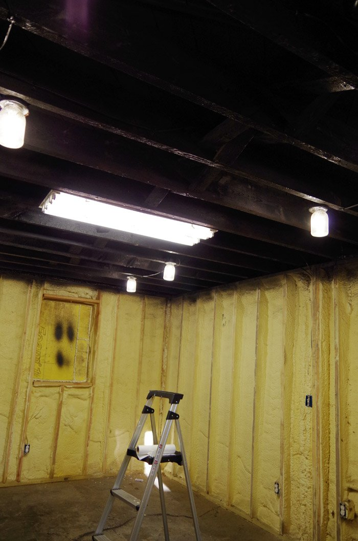Open industrial basement ceilings spray painted black for a theater and a reck room area in the downstairs basement ceiling blackspray paint.