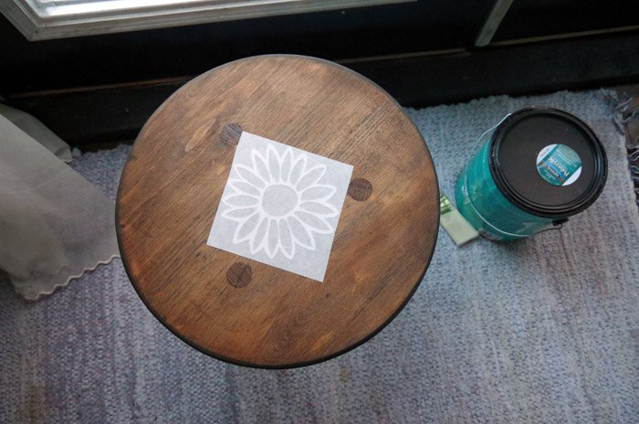 Three legged stool makeover for my bathroom project with dark paint, dipped legs and a sanded down dark stained topped with a flower vinyl decal