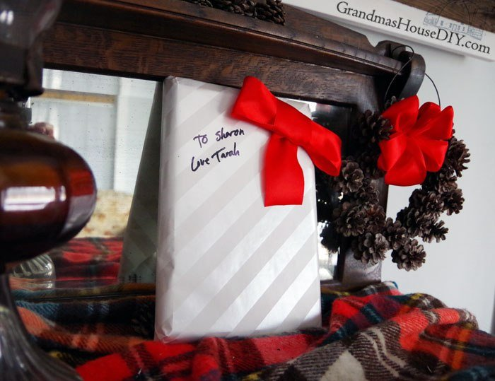 How to personalize basic gift wrap with a red bow. Striped silver wrapping paper dressed up for christmas, a birthday or even a baby shower