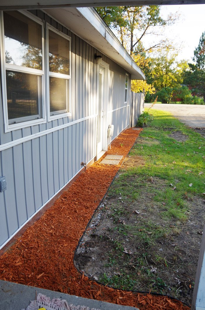 Improving the grade with garden edging, plastic, weed fabric and mulch. Covering the entire front of my home's foundation, the last step before siding.