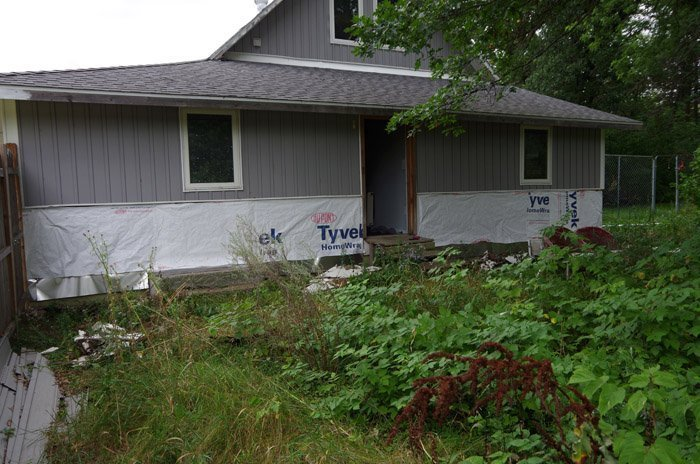 Tearing off the fake rock, fixing the old home wall behind it and replacing it with vertical siding on the wainscotting outside on my home
