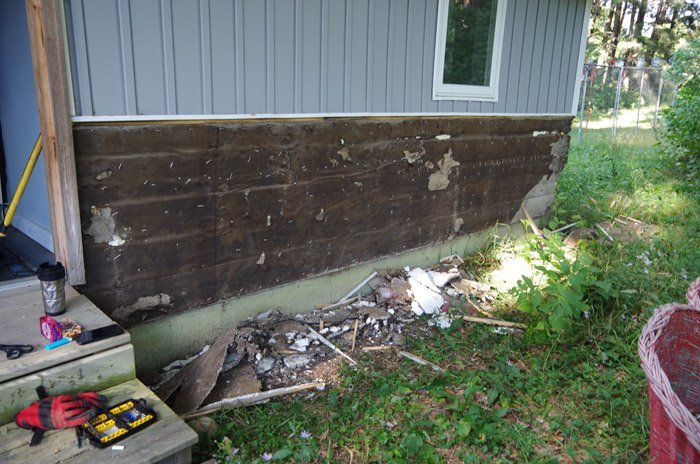 Tearing off the fake rock and stucco, fixing the old home wall behind it and replacing it with vertical siding on the wainscotting outside on my home