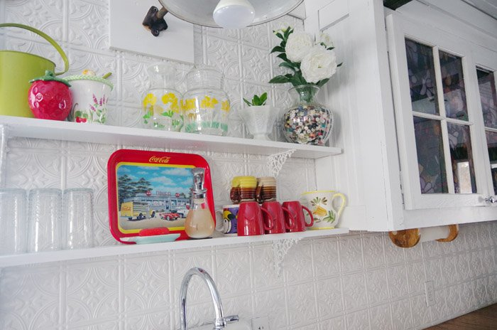Putting the open shelves above my kitchen sink to practical use without sacrificing the pretty, adding mugs cups and glasses