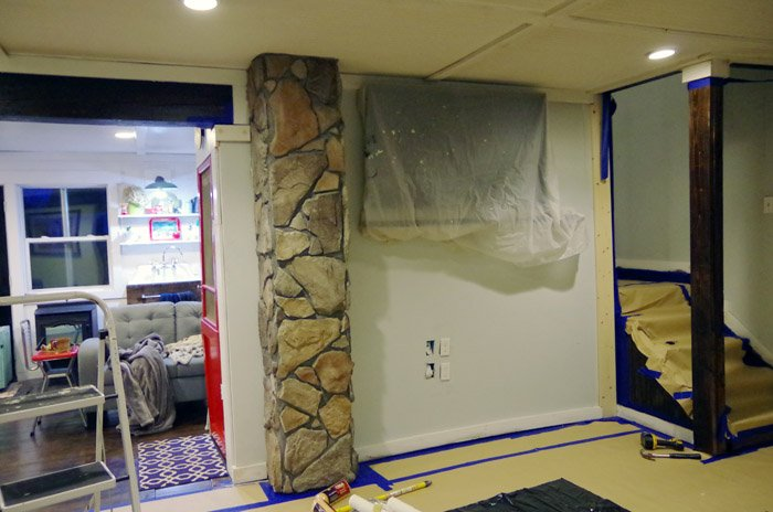 Painting out a faux stone chimney in white so I hate it a lot less now. Beginning the big remodel of my living room with a brand new sofa and paint!
