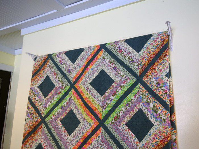 Hanging my grandma's old hand made quilt on my living room wall to showcase it, retire it and add some lovely color and history to my new living room!